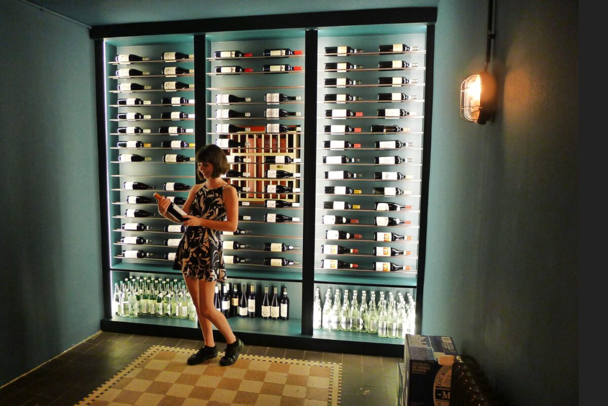 Woman-smiling-looking-at-a-wine-bottle-in-Kluis-restaurant-Amsterdam