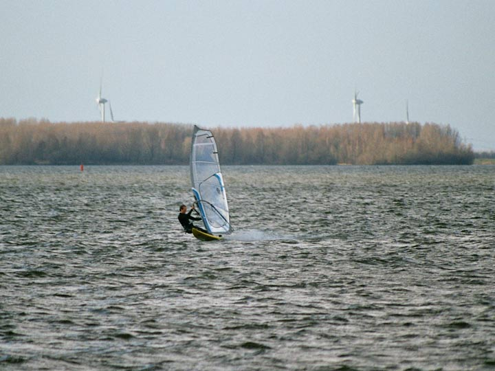 A windsurfer sails on a lake in the Netherlands with wind turbines in the background..