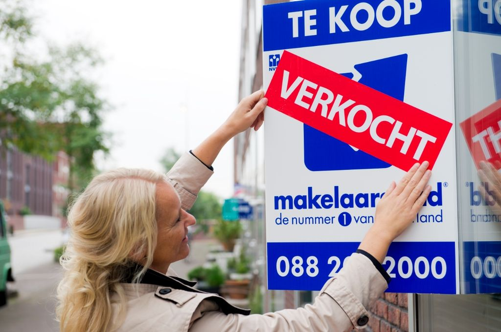 photo-of-real-estate-agent-putting-sold-sticker-on-house-in-netherlands