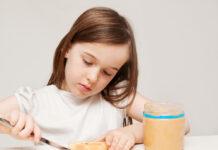 Young-Dutch-girl-wearing-white-t-shirt-making-peanut-butter-sandwhich