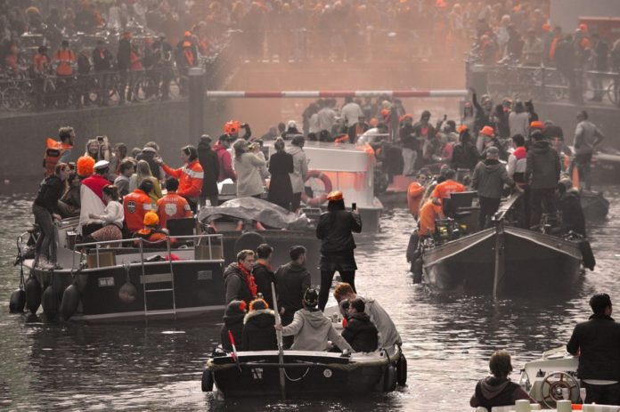 Boats on canals Amsterdam Kingsday