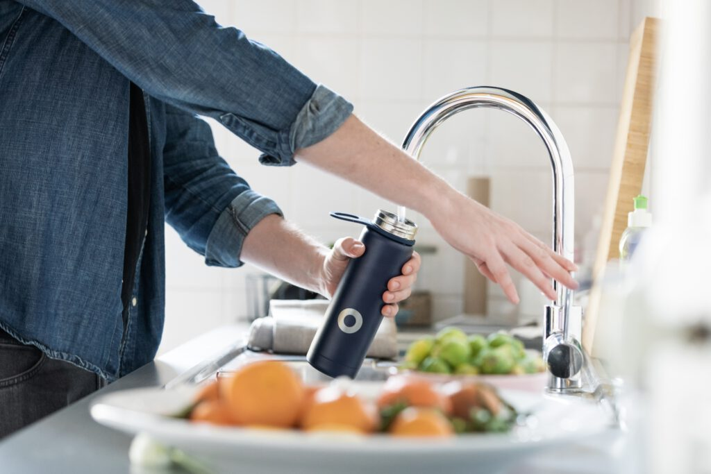 photo-of-person-filling-reusable-water-bottle