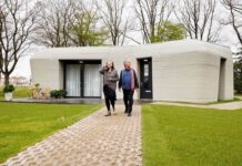 photo-of-a-couple-in-front-of-their-first-fully-3D-printed-house