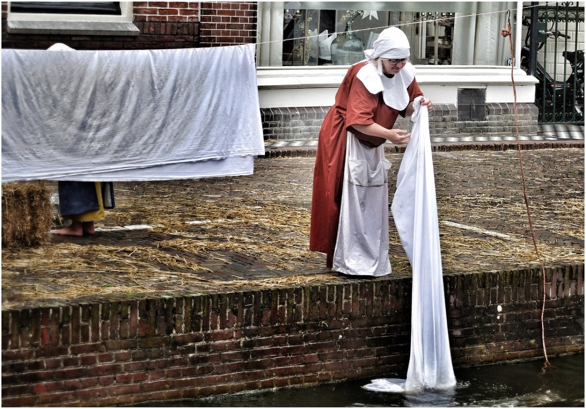 Woman dressed in historical Dutch clothes holds a sheet over a canal