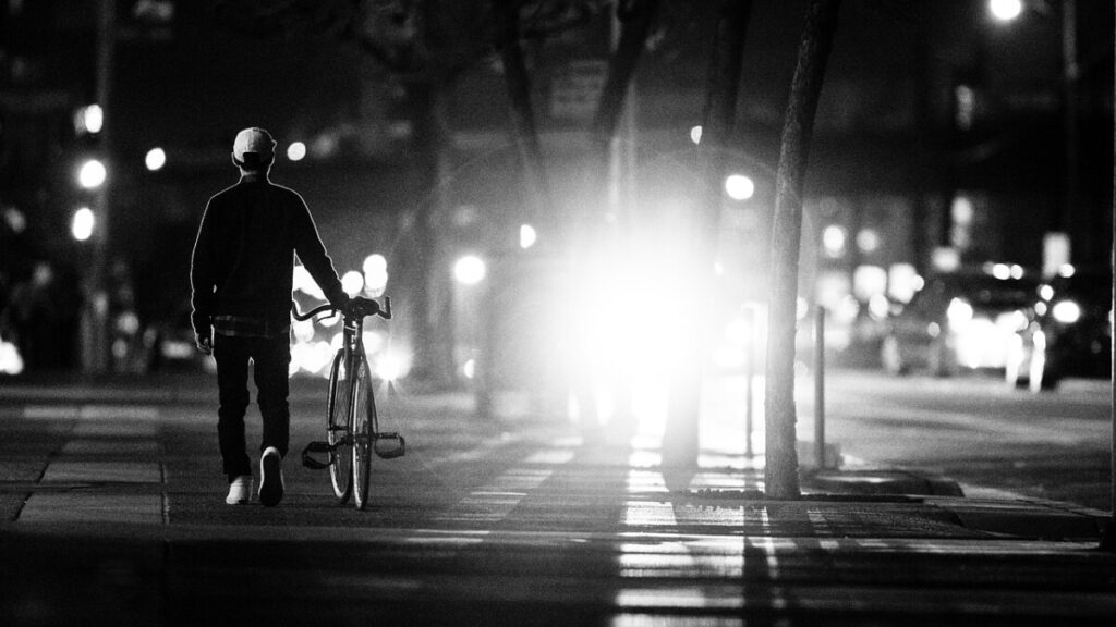 photo-man-walking-with-his-bike-at-night-in-the-netherlands