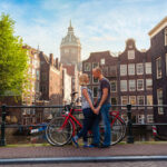 Two lovers person in Amsterdam on a background of multi-colored house in the Dutch style stand and hold hands.