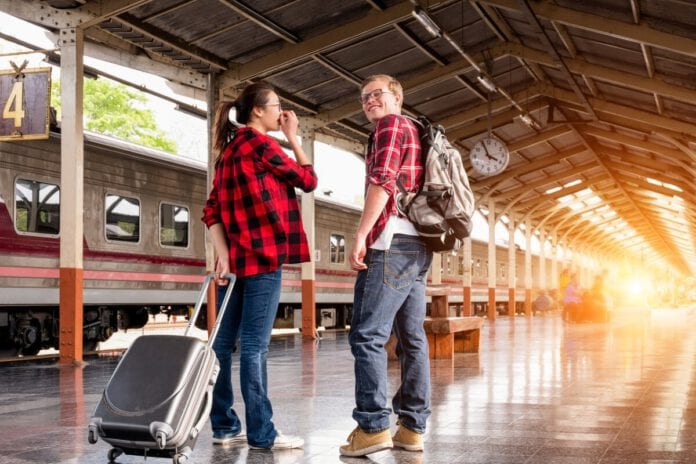 photo-of-couple-standing-on-train-platform