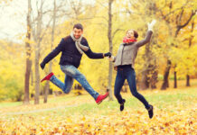 photo-of-couple-jumping-in-park-among-autumn-leaves