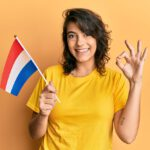 Young hispanic woman holding holland flag doing ok sign with fingers, smiling friendly gesturing excellent symbol