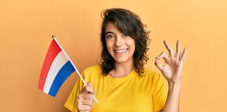 smiling-dutch-girl-holding-flag-and-making-ok-symbol