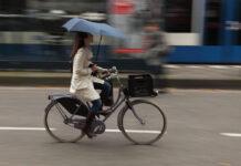 woman-biking-in-the-rain-with-an-umbrella