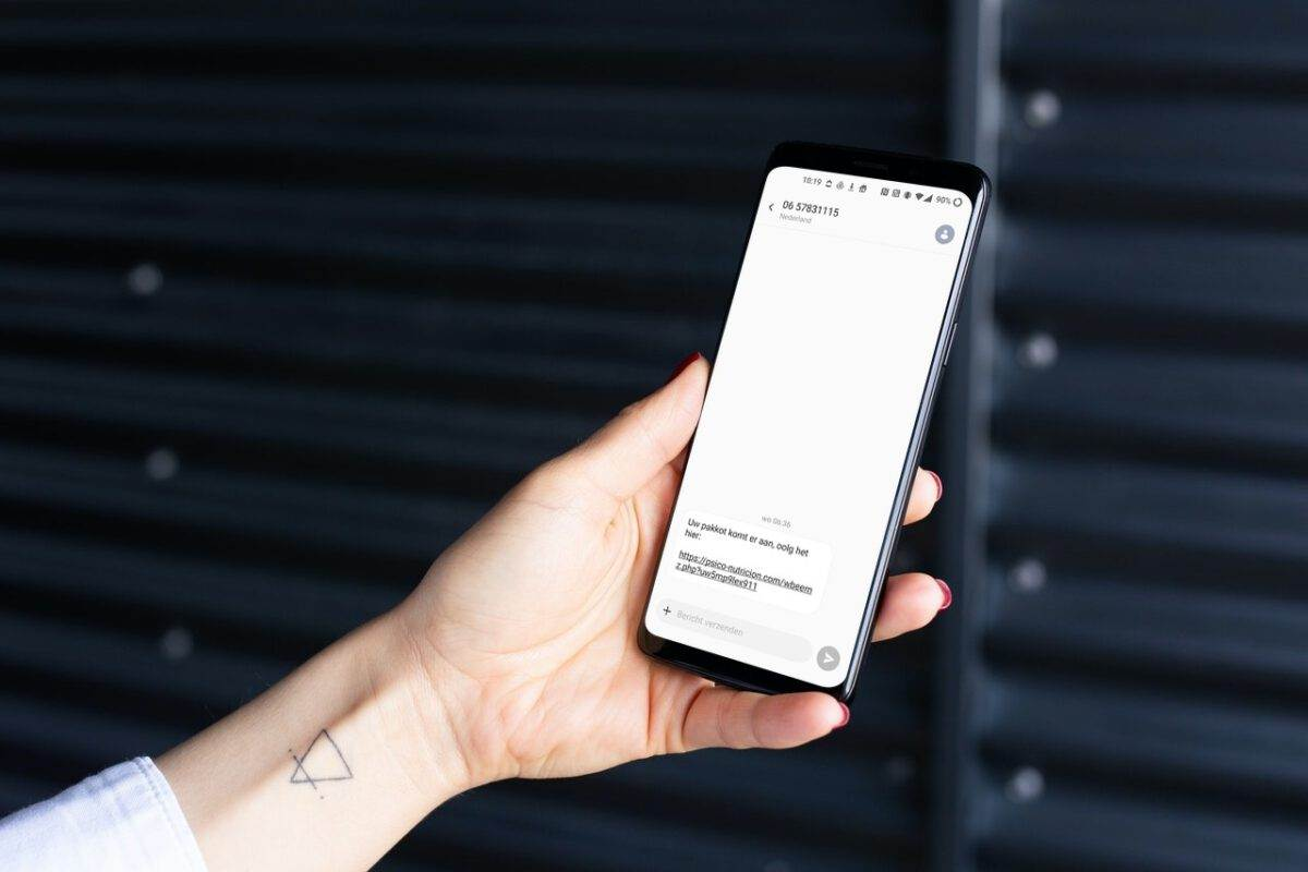 photo-of-a-hand-holding-a-smartphone-with-a-scam-message