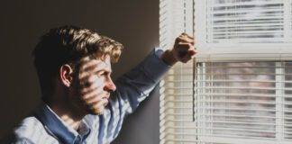 man-standing-in-front-of-window-blinds