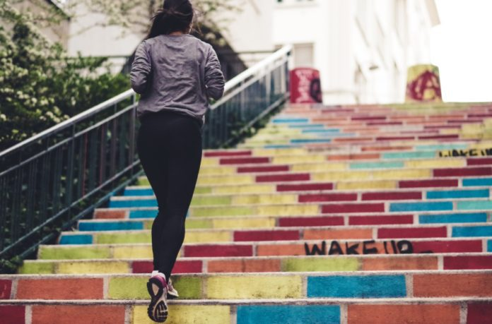Girl jogging up colourful staircase