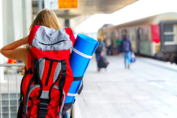 young-woman-backpacking-train-station