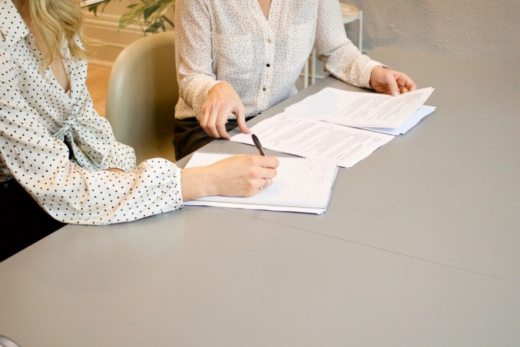 Photo-of-people-sitting-at-table-with-documents-registering-in-the-Netherlands-Registration