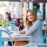 Woman drinking coffee and writing notes in cafe