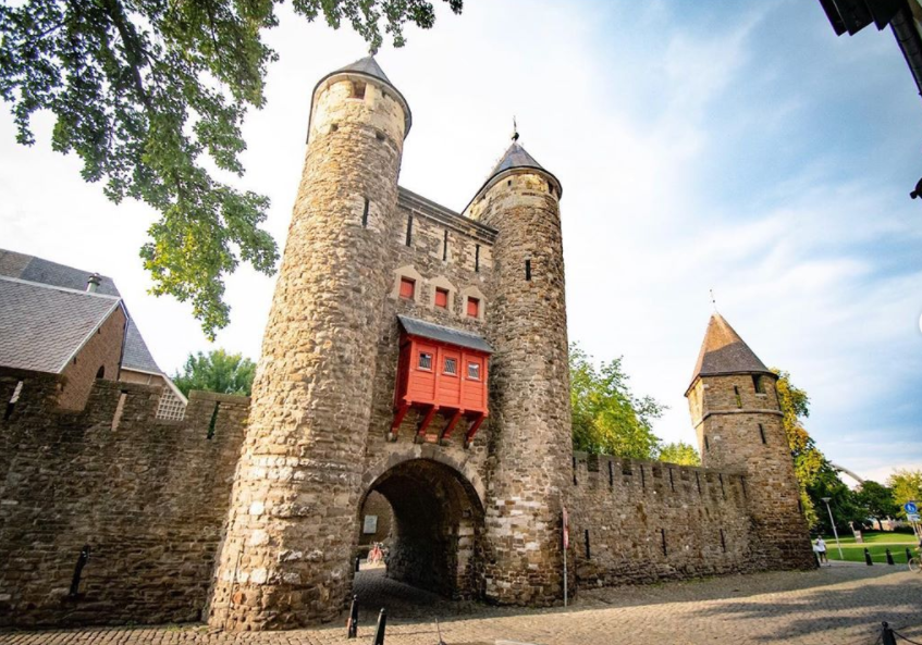 helpoort-old-stone-gate-with-two-towers-and-long-stone-brick-wall-either-side