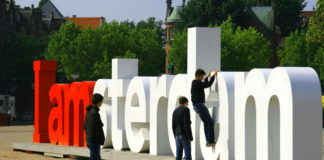 people climbing on the iamsterdam sign