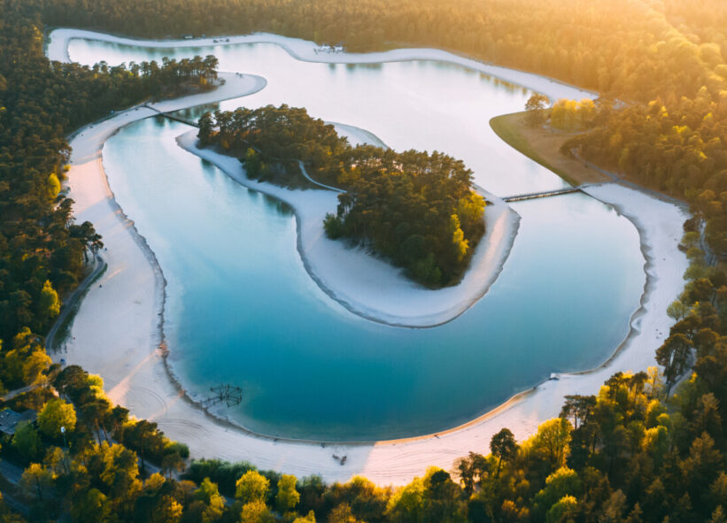 View from above as the evening sun shines on a bright blue doughnut-shaped lake, Henschotermeer.