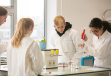 international-students-in-lab-coats-doing-experiment