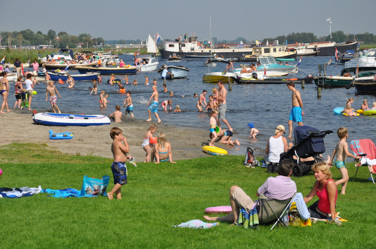 A crowd of people enjoy the grassy beach with boats in the background.