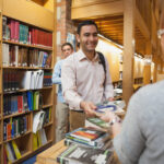Mature female librarian handing a book to young man in library