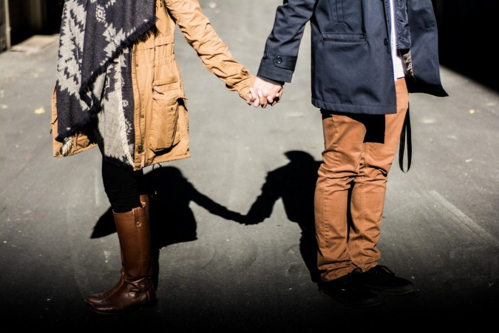 a couple holding hands on the street