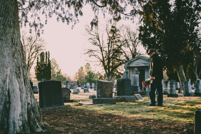 man-standing-in-cemetery-at-grave-after-death