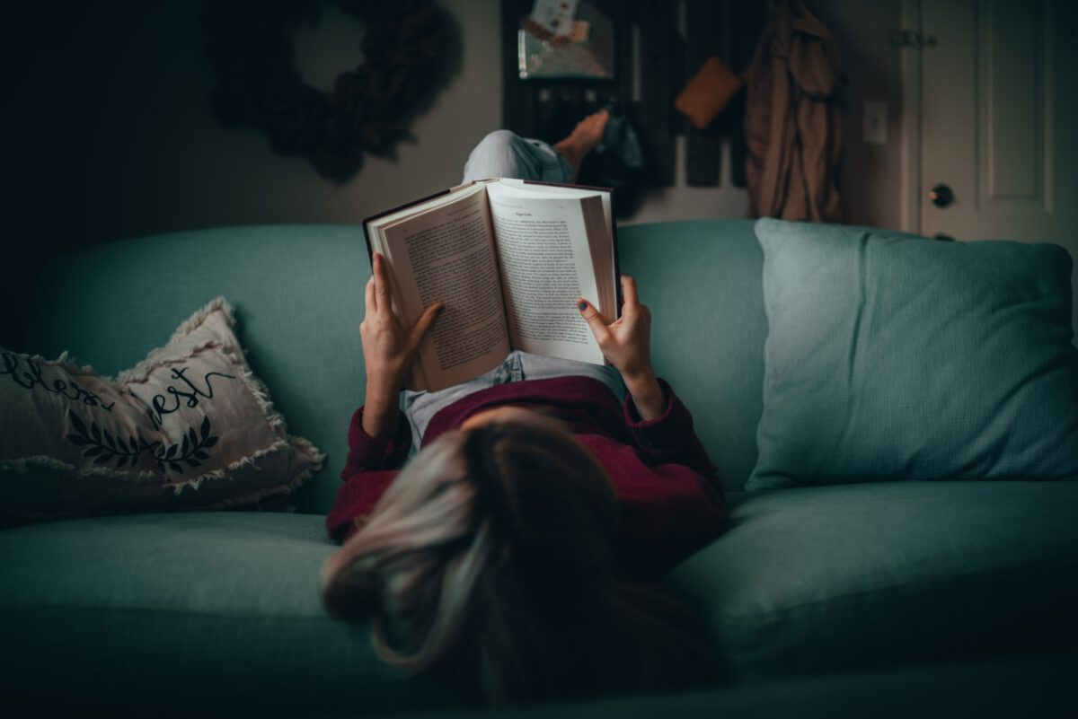 Photo-of-woman-reading-book-on-couch