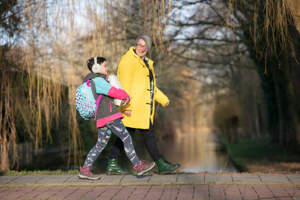 teacher-and-young-student-walking-to-school-past-canal-in-netherlands