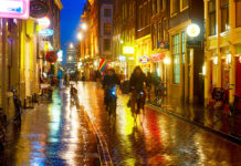 photo-of-people-cycling-in-amsterdam-street-in-rain