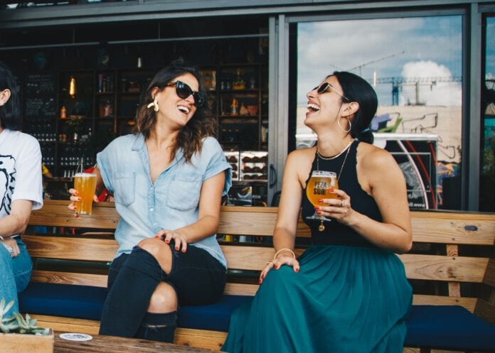 photo-of-two-women-drinking-beers-in-sun