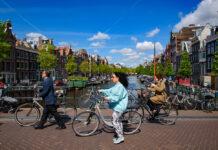 photo-of-people-riding-bikes-along-amsterdam-bridge