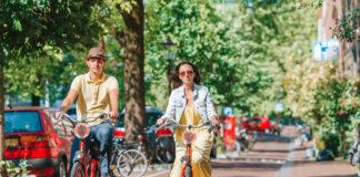 photo-of-couple-riding-bikes-through-amsterdam