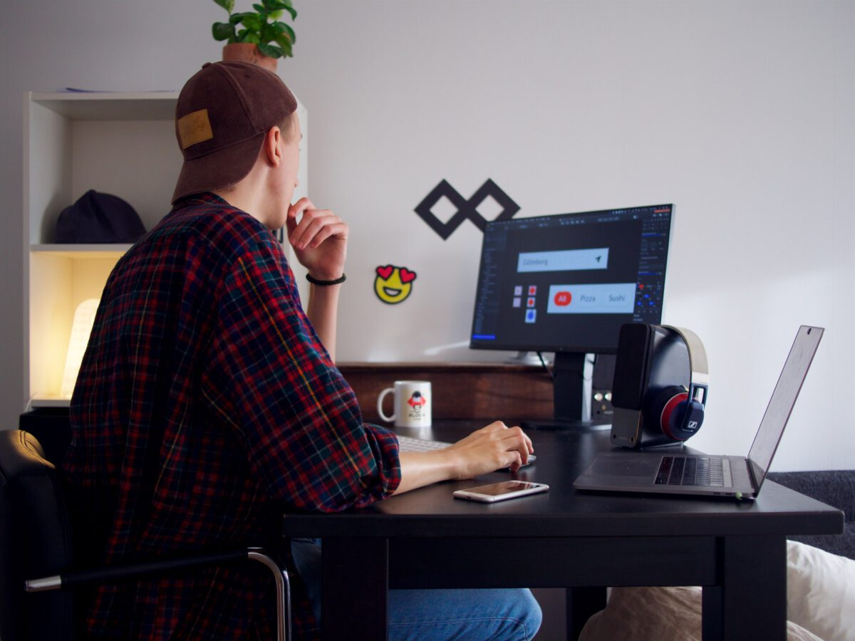 Photo-of-freelance-worker-sitting-at-desk-with-computers