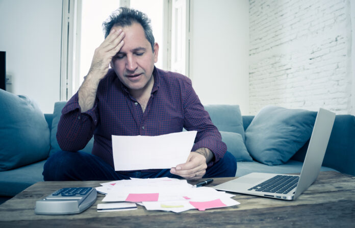 man-holding-bill-being-stressed
