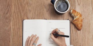 photo-of-dutch-woman-writing-in-agenda-with-coffee-and-croissant