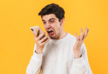 angry-man-yelling-at-his-phone-with-crazy-face-orange-background