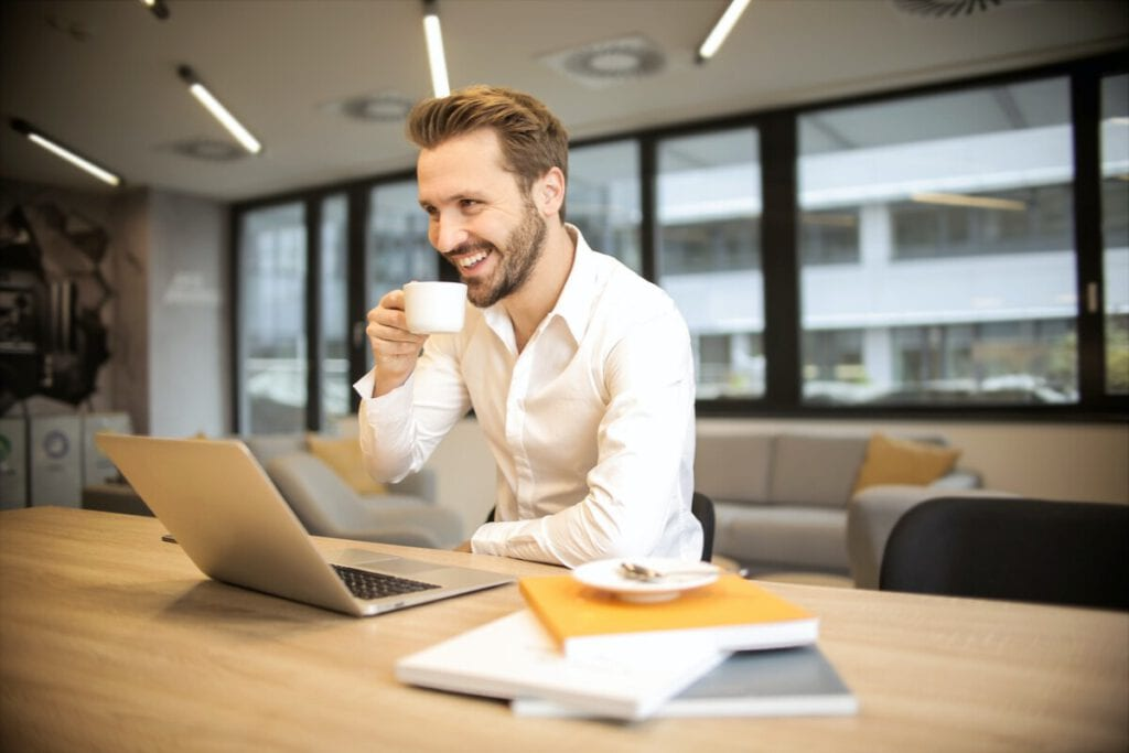 photo-of-man-with-sponsored-job-in-netherlands-smiling-holding-coffee