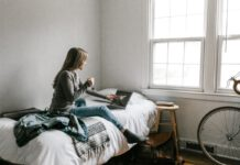 girl-in-student-house-in-netherlands-amsterdam-sitting-on-bed