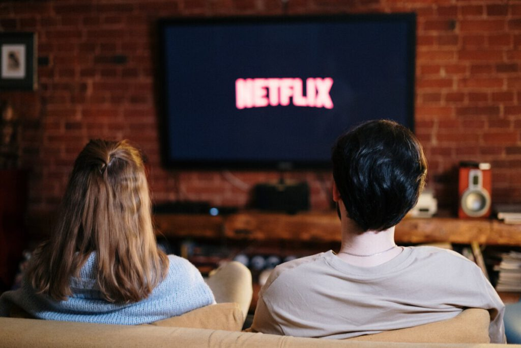 Photo-of-couple-sitting-on-couch-watching-tv