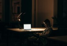 man sitting in dark at computer