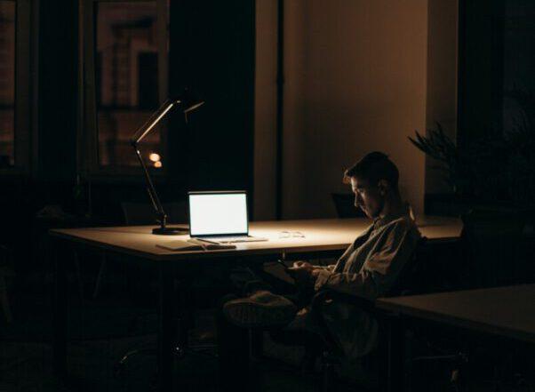 man sitting in dark at computer