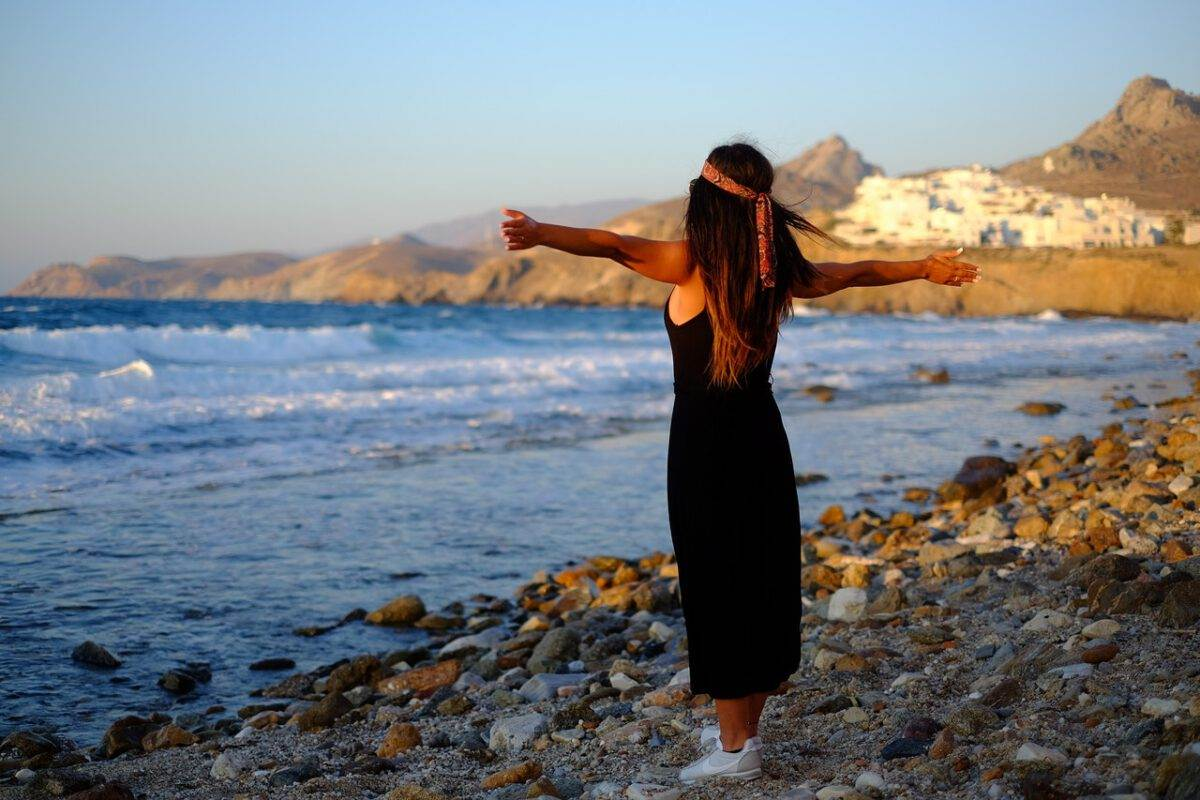 Photo-of-woman-standing-on-greek-beach-with-arms-out