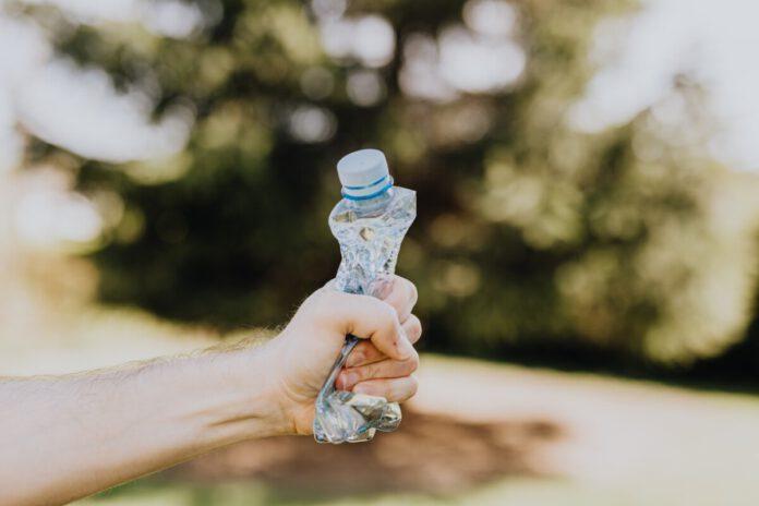 hand crushing plastic bottle