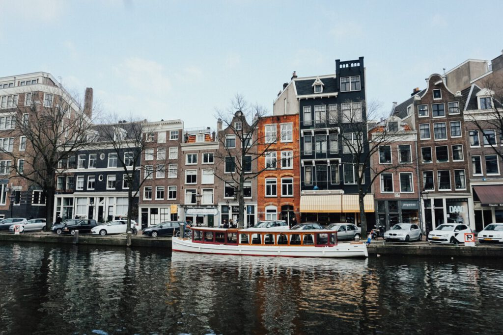 photo-of-canal-houses-in-amsterdam-as-a-boat-floats-on-the-river