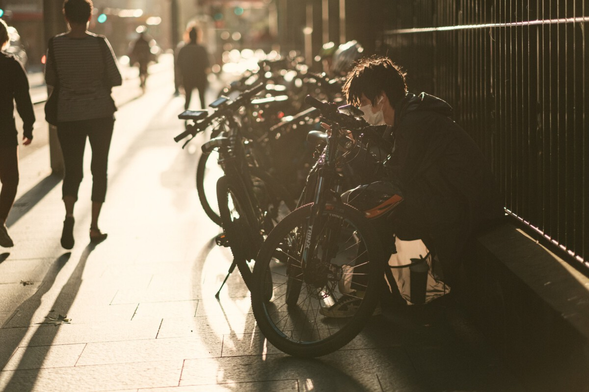 photo-of-a-man-wearing-a-face-mask-sitting-in-front-of-bikes