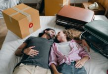 photo-of-girl-and-boy-laying-on-bed-with-suitcases-after-moving-to-holland