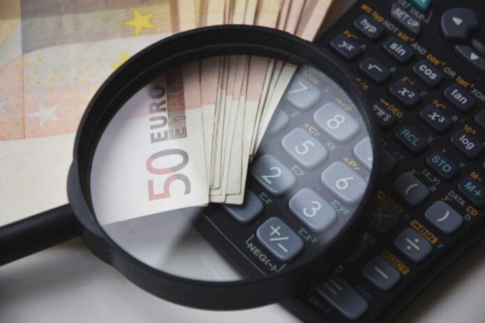 photo-of-magnifying-glass-on-calculator-and-money-tax